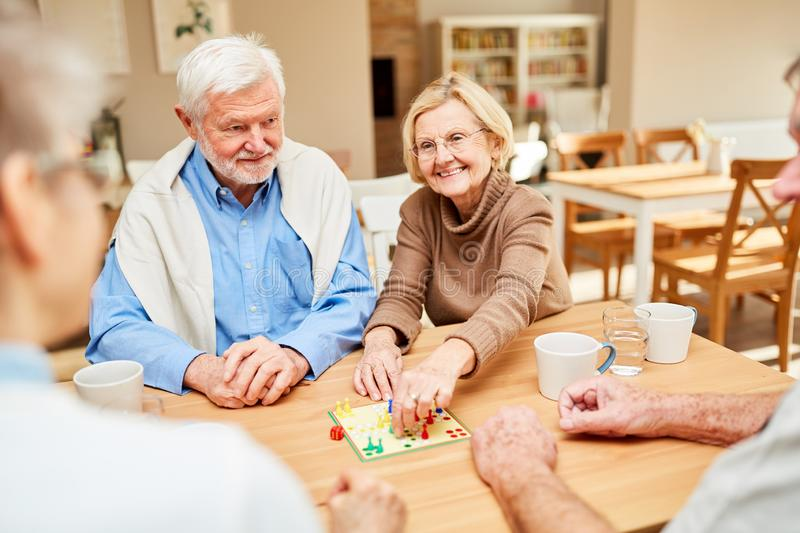 Group of seniors enjoys board game royalty free stock images