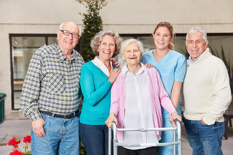 Group of seniors with geriatric nurse in the retirement home. Group of seniors as friends laugh happily with geriatric nurse in retirement home stock photography