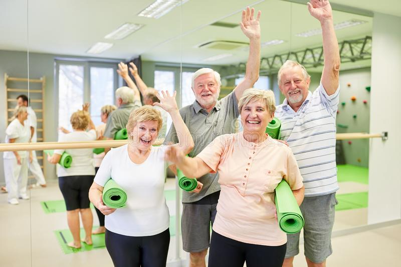 Group of seniors is having fun together in the gym. Group of seniors having fun together at the fitness class in the gym and waving to the camera royalty free stock photography