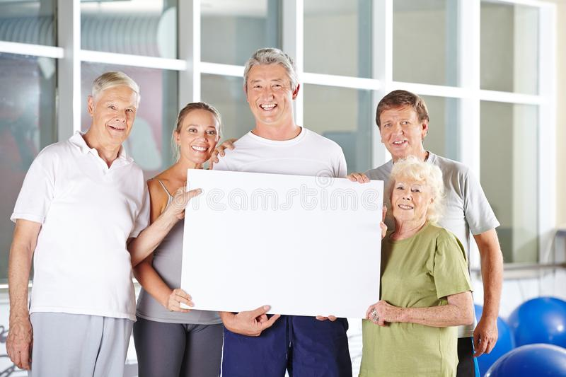 Group of seniors holds blank billboard in the fitness center royalty free stock image