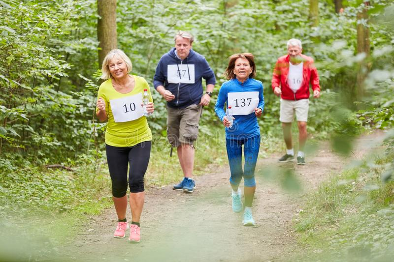 Group of seniors jogging training. Group of seniors trains fitness while jogging or makes a competition stock photo