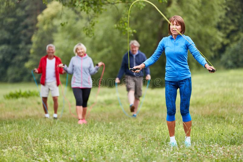 Group of seniors jumping rope. Group of seniors while jumping rope in a endurance fitness course in the park stock photography