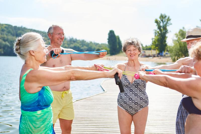 Group of seniors at the lake is doing gymnastics. Group of seniors on the lake shore doing gymnastics exercise with skipping rope as a fitness workout royalty free stock photo
