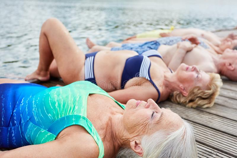 Group of seniors relaxing on a footbridge. Group of seniors lying relaxed on a jetty on the lake in summer on vacation royalty free stock photos