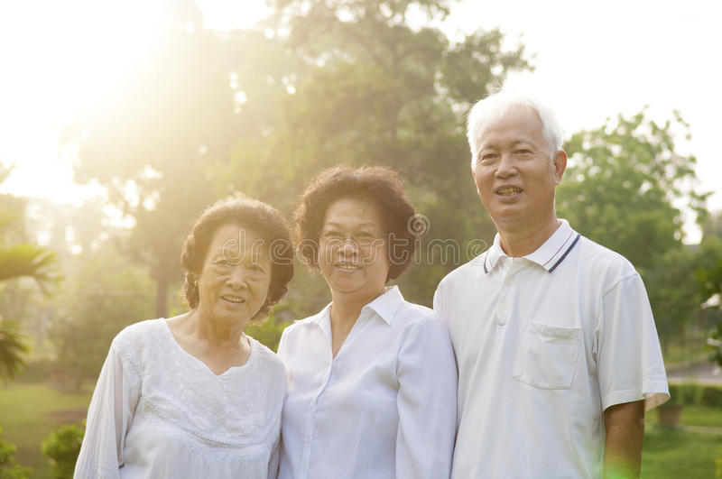 Group of seniors people. Group of healthy Asian seniors having good time at outdoor nature park, in morning beautiful sunlight at background stock image