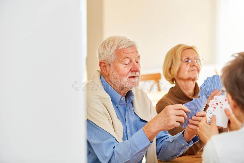 Group of seniors playing cards at home. Group of seniors playing card games together in a retirement home or at home stock photo