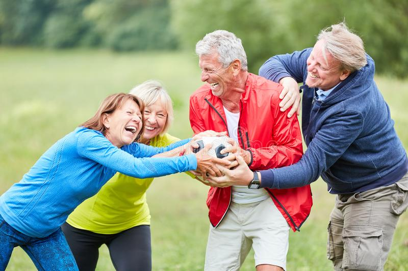 Group of seniors playing with a soccer ball. Group of seniors is having fun while racking and playing with a football in the park stock photography