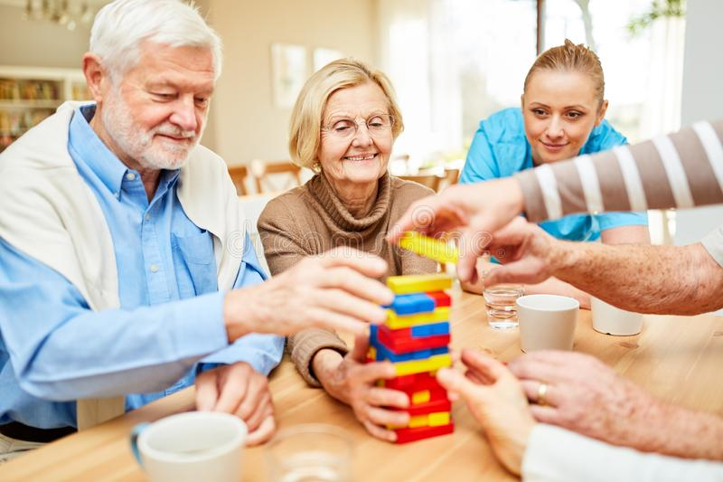Group of seniors playing with building blocks in retirement home. Group of seniors plays together with colorful building blocks in retirement home stock images