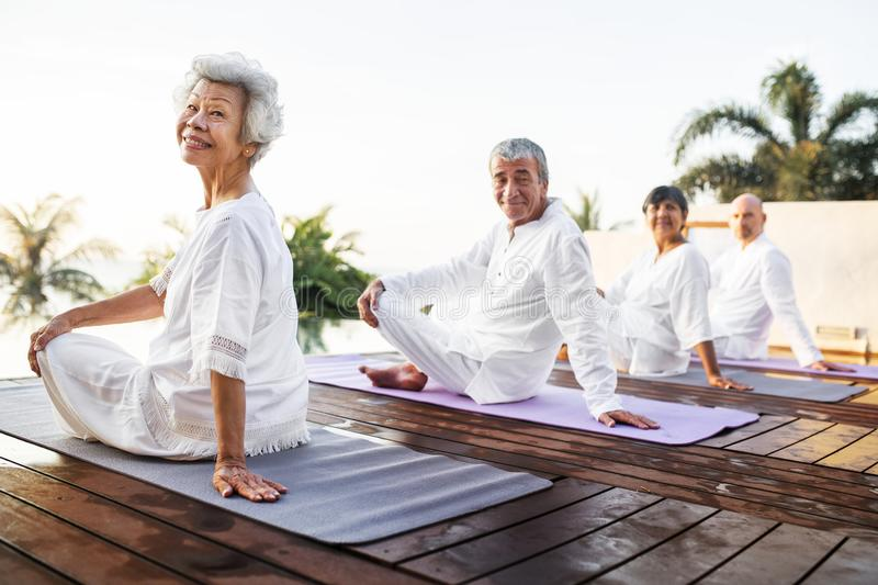 Group of seniors practicing yoga stock images