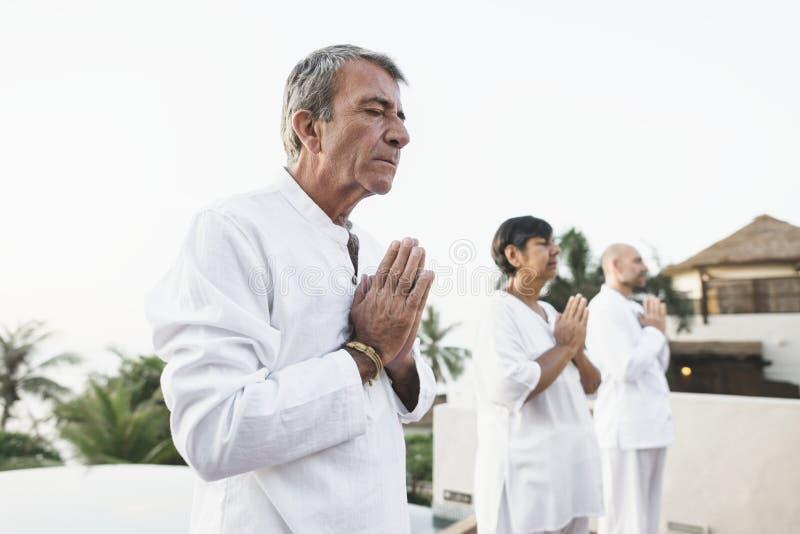 Group of seniors practicing yoga stock photos