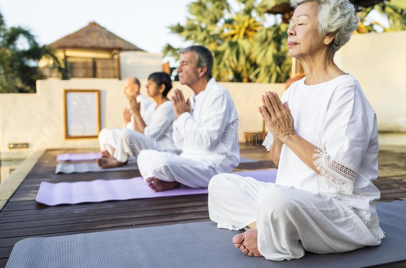 Group of seniors practicing yoga in the morning stock photo