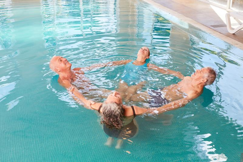 Seniors in the pool do aqua gymnastics. Group of seniors in rehab in the pool together do aqua gymnastics stock photo