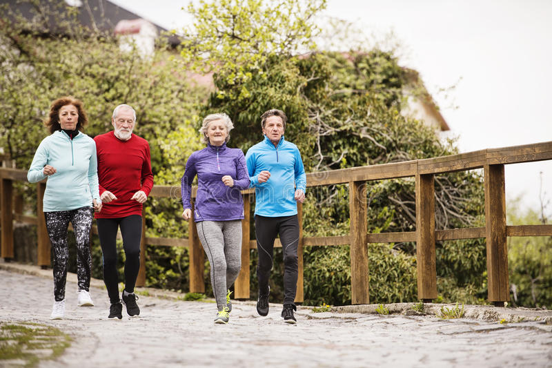 Group of seniors running outdoors in the old town. stock photography