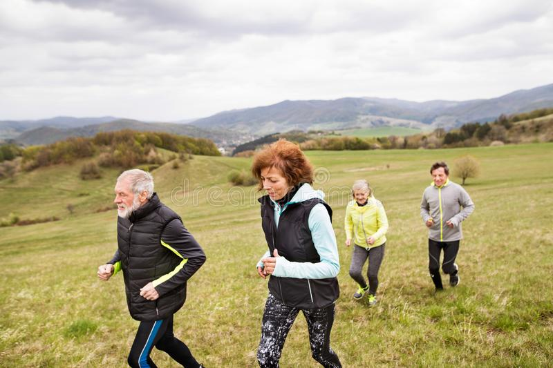 Group of seniors running outside on the green hills. Group of active seniors running together outside on the green hills royalty free stock photography