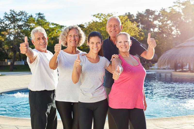 Group of seniors in a spa vacation at the pool with thumbs up. Group of seniors in a spa vacation at the pool is happy with thumbs up royalty free stock photos