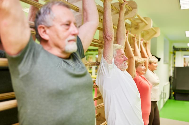 Group of seniors stretching and stretching. On the wall in physiotherapy stock images