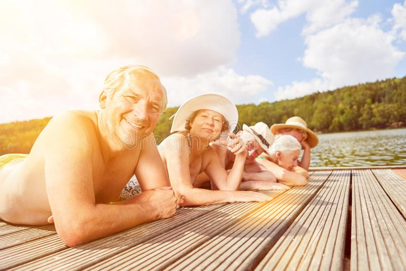 Group of seniors sunbathing by the lake. Happy group of seniors sunbathing at the lake in summer royalty free stock photography