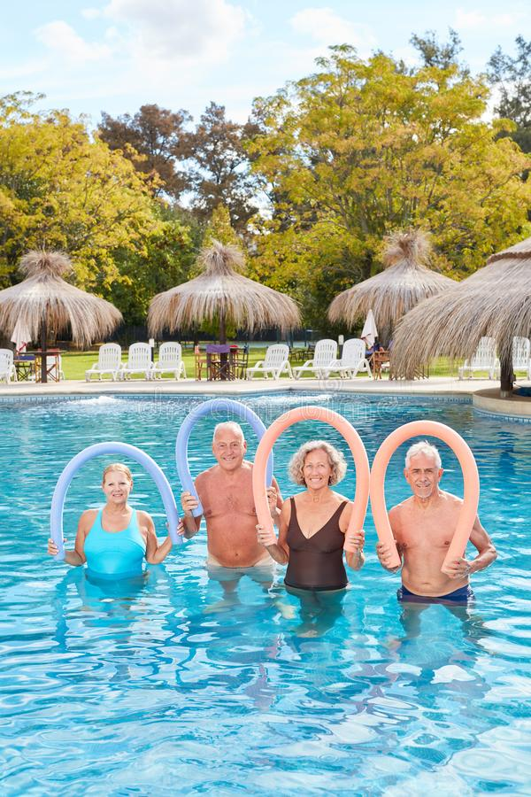 Group of seniors with swimming noodle in the pool. Group of seniors standing with swimming noodle in the swimming pool at the spa hotel stock image