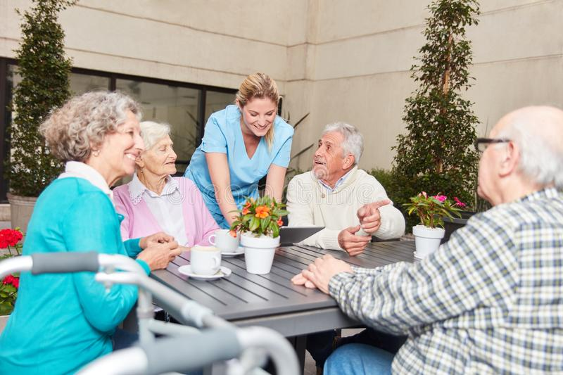 Group of seniors talking in retirement home. Nursing and group seniors talking in the lounge in retirement home stock image