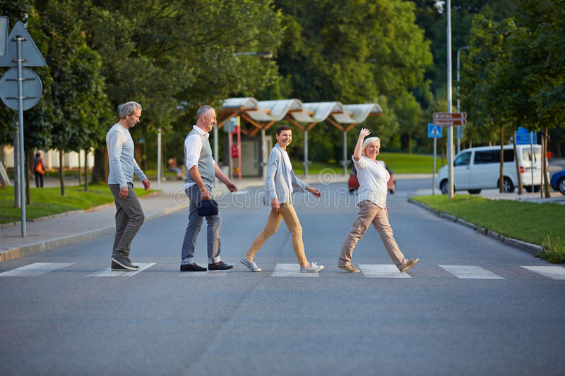 Group of seniors walking over crosswalk. Happy group of seniors walking over crosswalk in a line royalty free stock photos