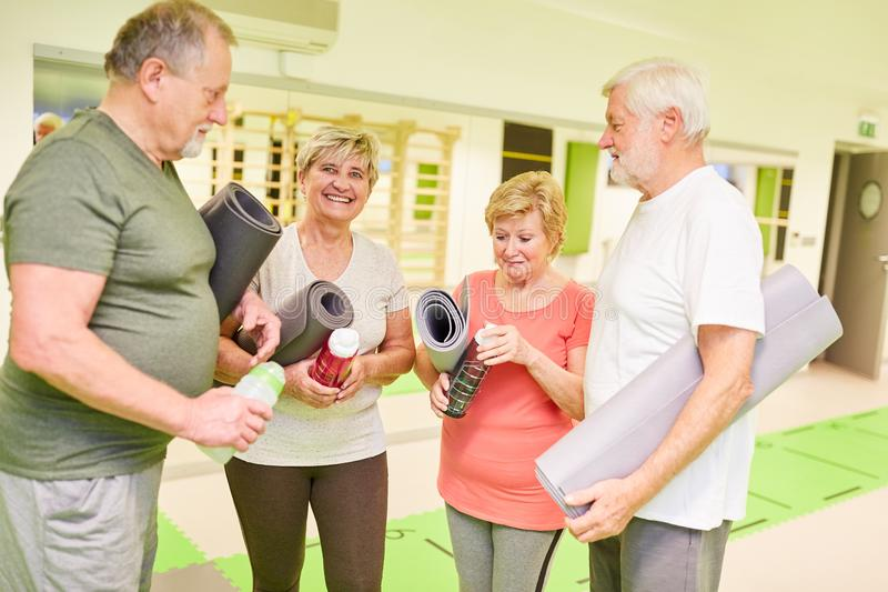 Group of seniors with yoga mat in the fitness center. During a break during small talk stock photography