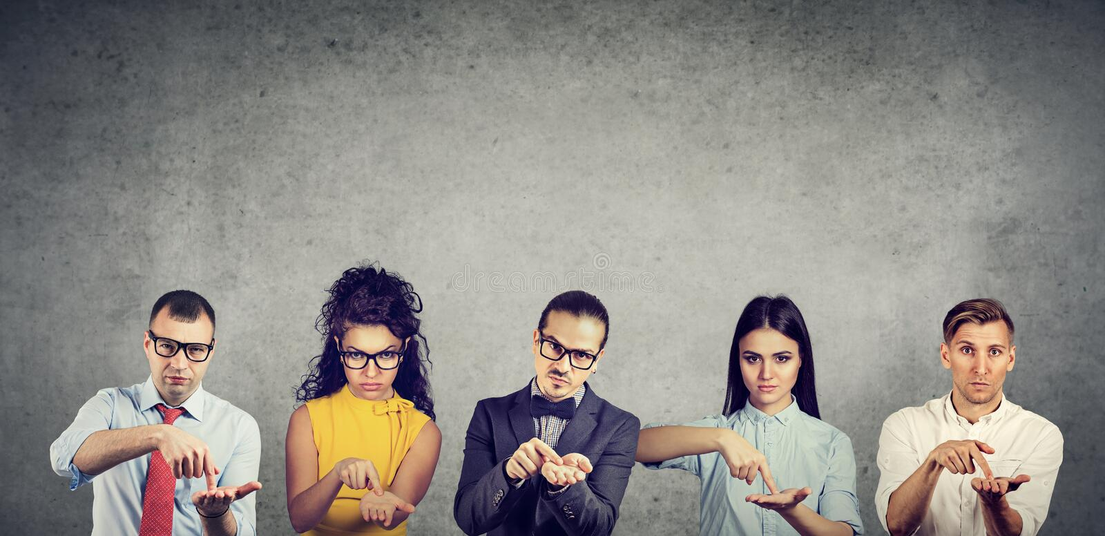 Group of serious business people men and women asking for more money stock images