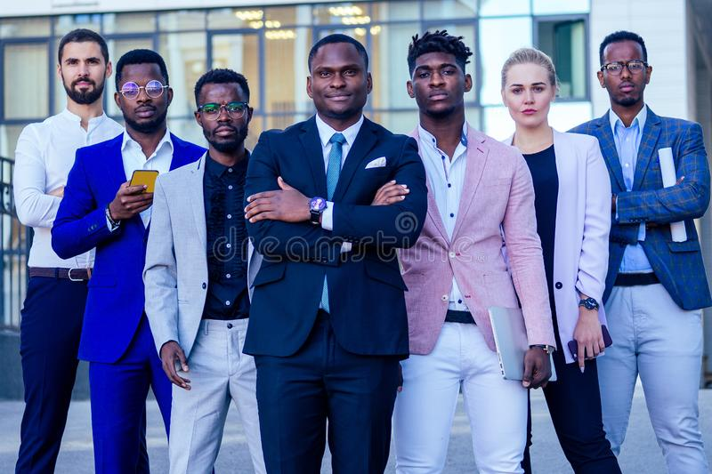 A group of seven successful business people men and woman in stylish suits standing and looking proudly outdoors stock photography