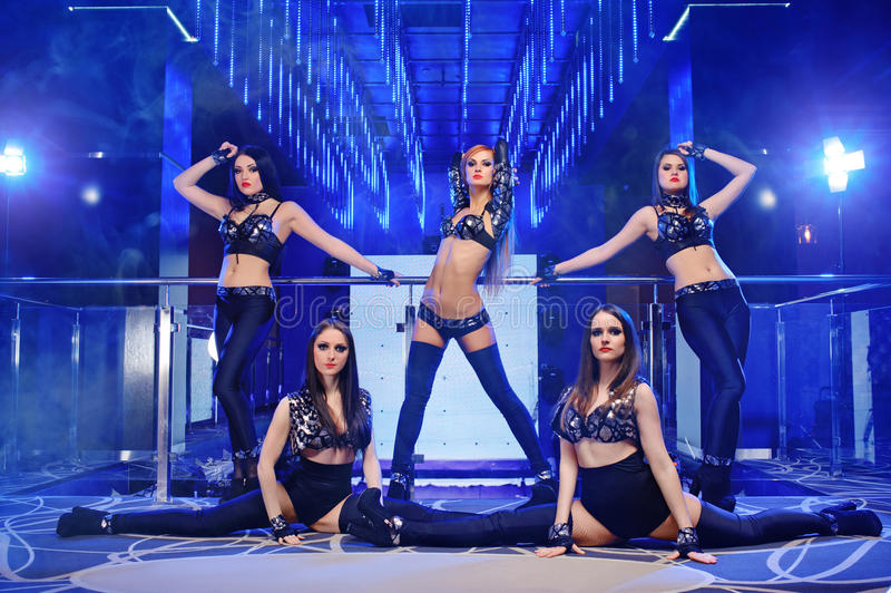 Group of go-go dancers wearing black outfits. Beautiful flexible graceful female dancers posing at the nightclub together seductive provocative erotic entertain stock photos