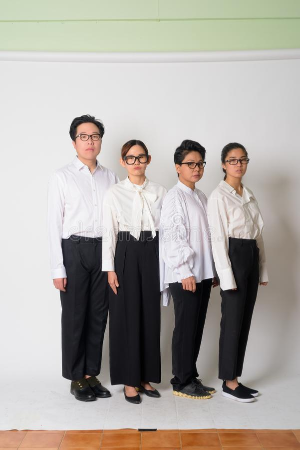 Group shot of Asian business people with eyeglasses together. Studio group shot of four Asian business people as team together against white background stock images
