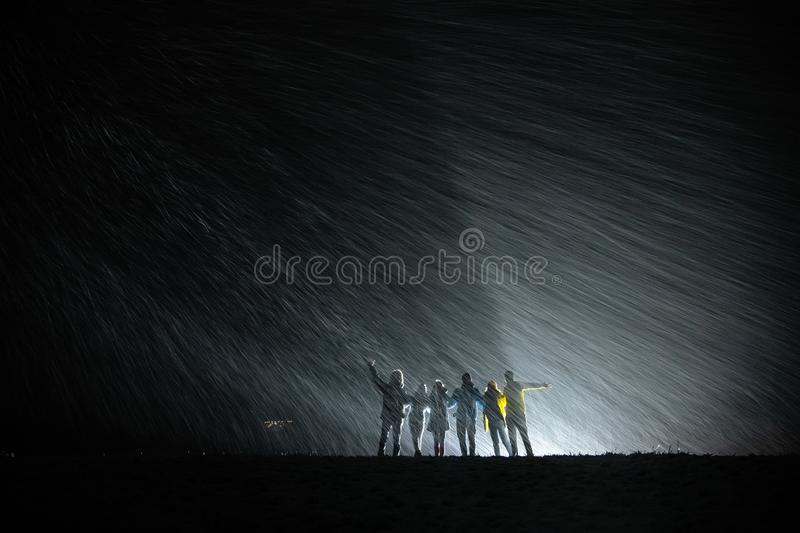 Group of silhouettes against snowfall and back light stock image