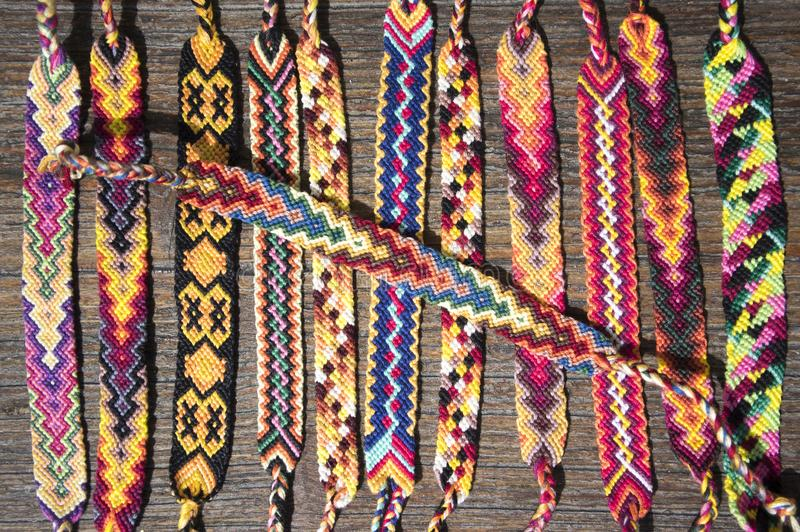Group of simple handmade homemade natural woven bracelets of friendship on wooden background, rainbow colors, checkered pattern. One by one stock photo
