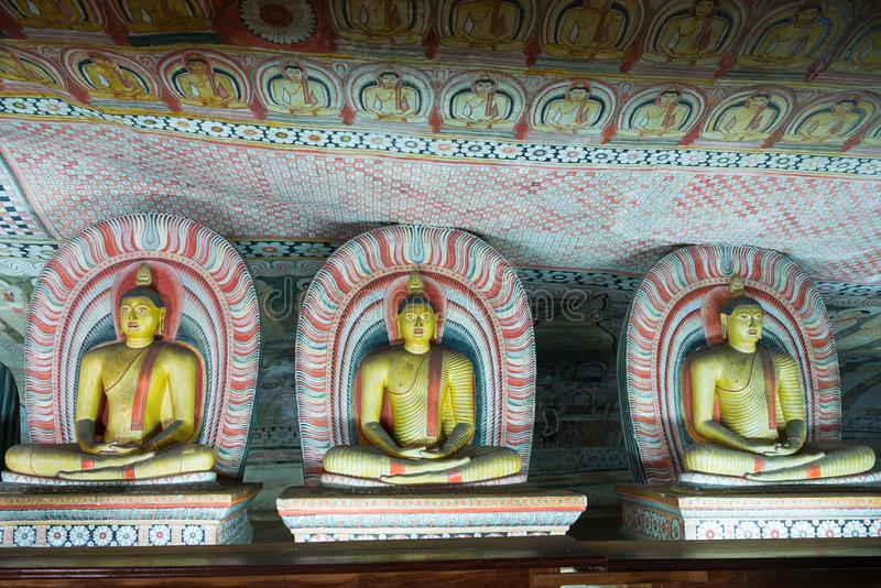 Group of sitting Buddha statues in cave buddhist temple. With bright painted murals on walls and ceiling in Dambulla Golden temple in Sri Lanka stock images