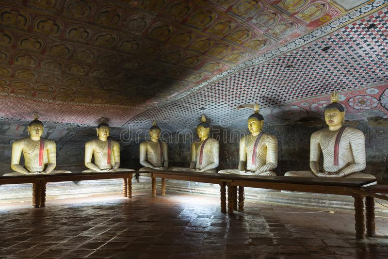 Group of sitting Buddha statues in cave buddhist temple. With bright painted murals on walls and ceiling in Dambulla Golden temple in Sri Lanka royalty free stock images