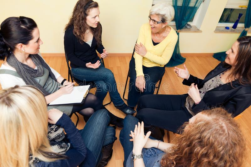 Group Of Women Sitting In A Circle, Discussing. A group of six women are sitting in a circle, discussing stock photo