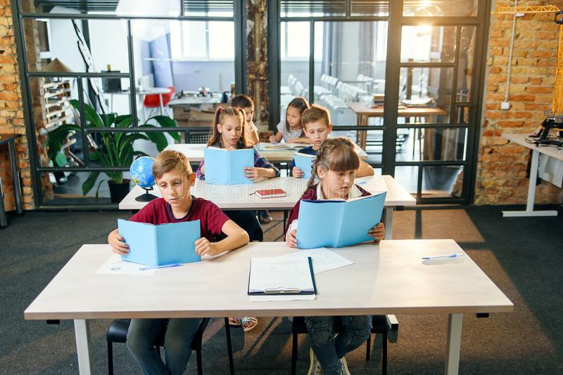 Group of six young happy pupils sit at their desk and reading educational books in the lesson. stock photo