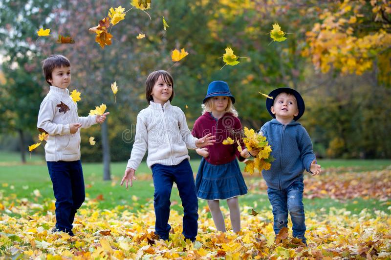 Group of small children in the park, having fun throwing leaves. Autumn time, happiness, leisure, friendship concept stock images