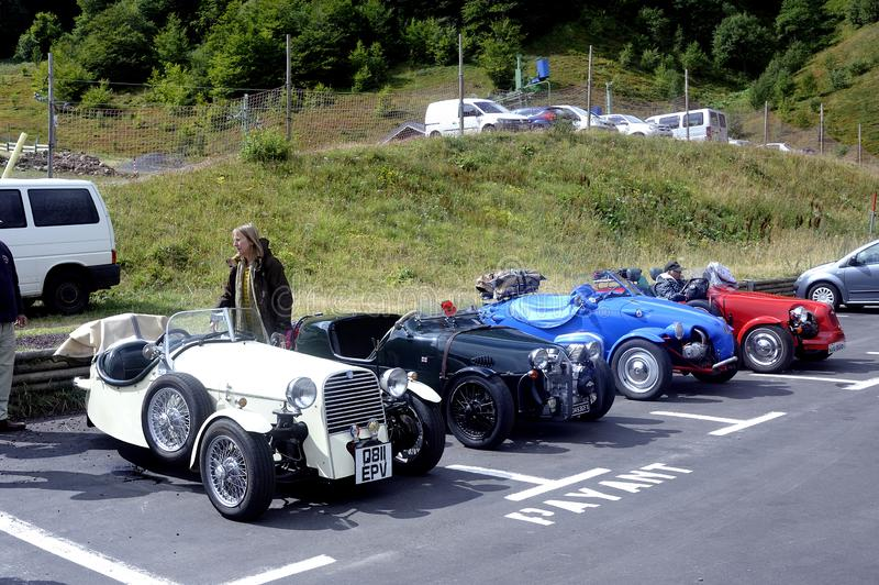 Group of small English cars with three wheels. At the feet of Puy de Sancy stock image