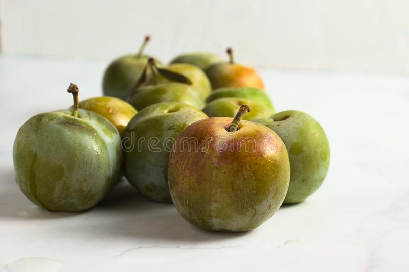 Group of small greengage plums on white marble. Closeup royalty free stock images