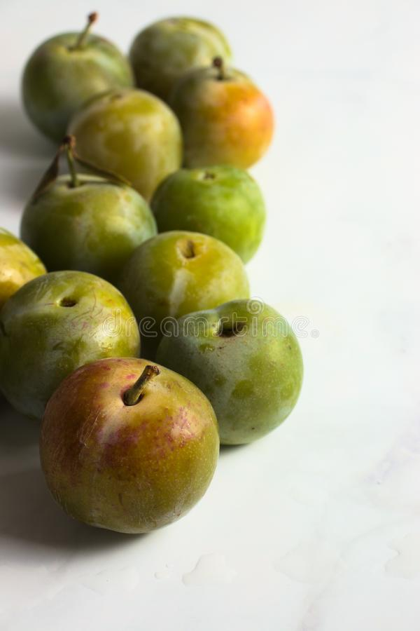 Group of small greengage plums on white marble. Closeup stock photography
