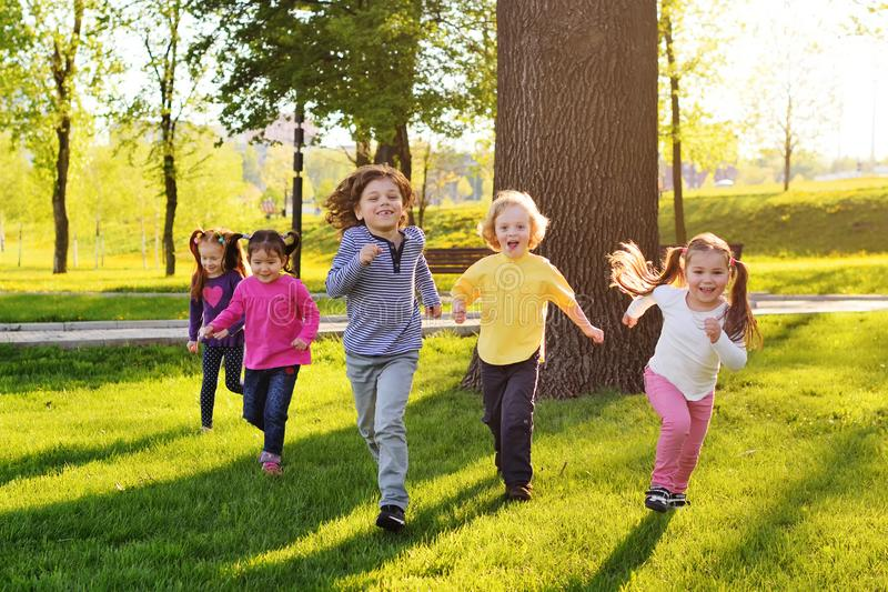 A group of small happy children run through the park in the background of grass and trees. stock images