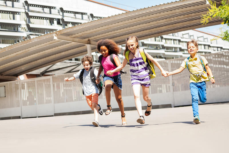 Group of small kids run near school together. Group of kids holding hands wearing backpacks running near school royalty free stock photography