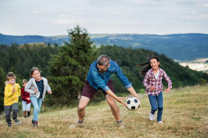 Group of school children with teacher on field trip in nature, playing with a ball. stock image