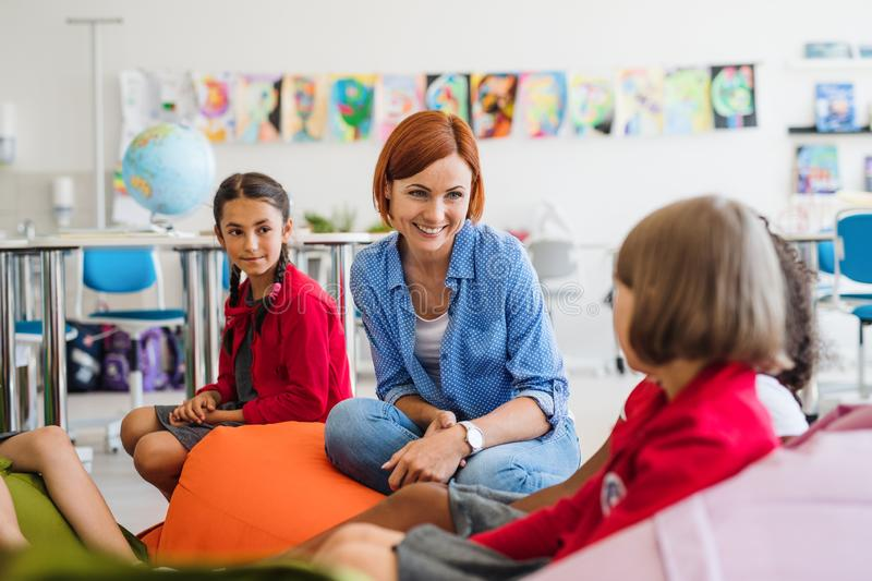 Group of small school kids with teacher sitting on bean bags in class, talking. stock photo