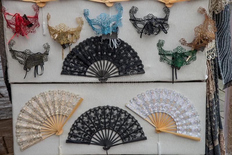 Group of small vintage Venetian carnival masks in fabric and fans. royalty free stock photo