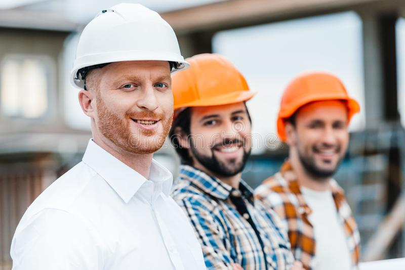 Group of smiling architects in hard hats looking. At camera royalty free stock image