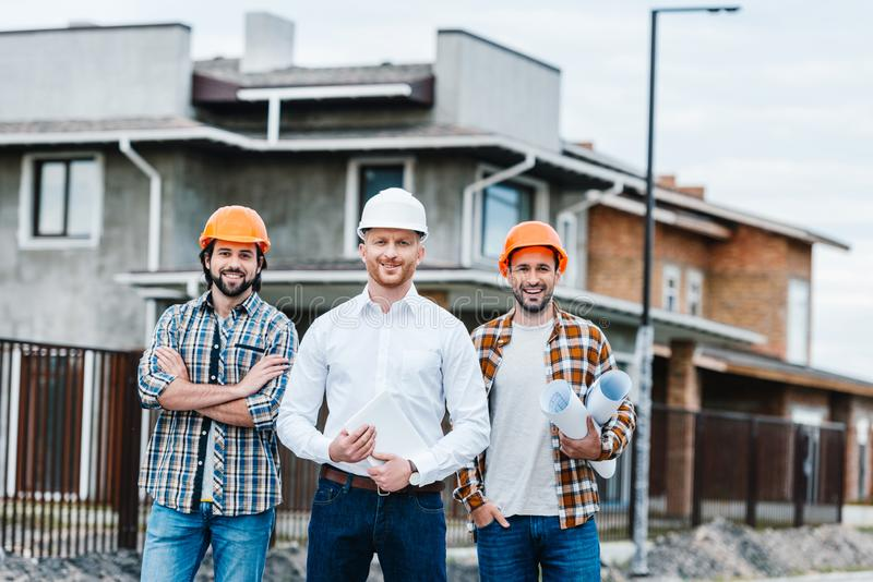 Group of smiling architects in hard hats looking at camera. On building street royalty free stock image