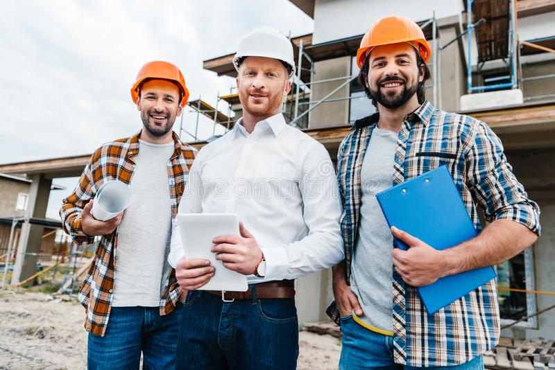 Group of smiling architects in hard hats looking at camera in front of. Building house royalty free stock image