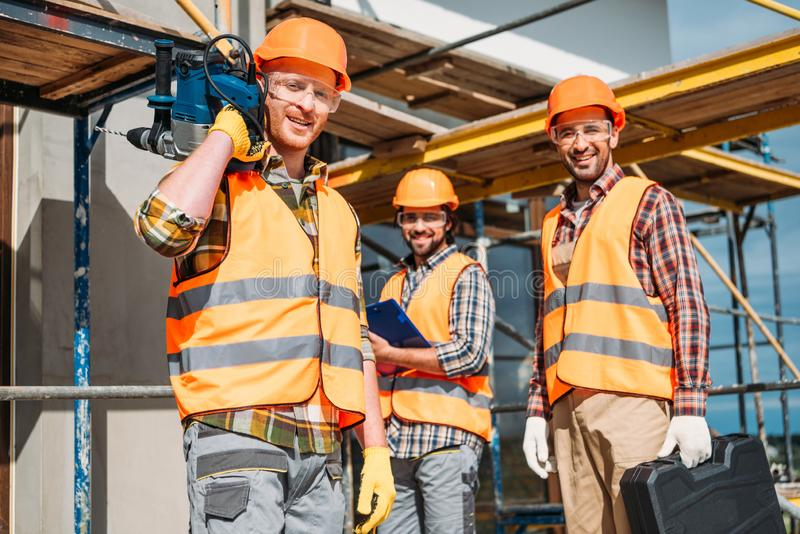 Group of smiling builders with building equipment standing at construction site and looking. At camera royalty free stock image