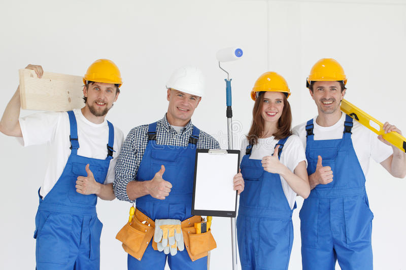 Group of smiling builders. In hardhats with tools indoors stock photography