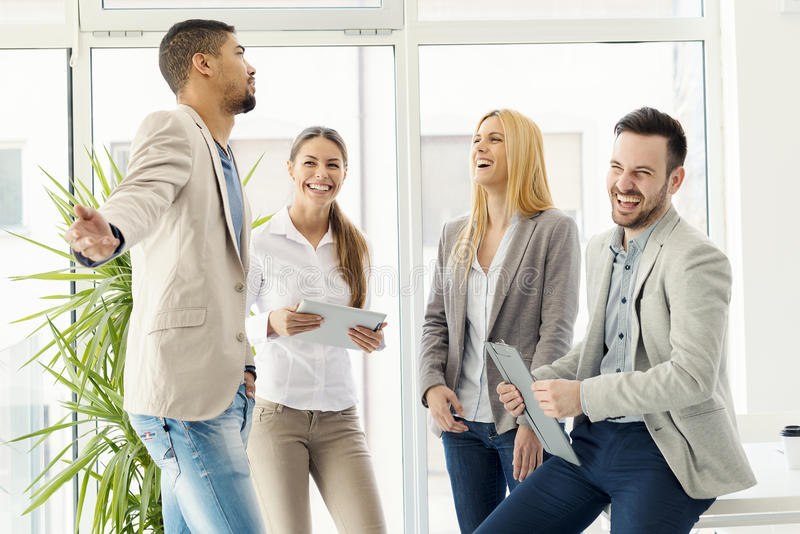 Group of smiling business people standing and communicating stock photography